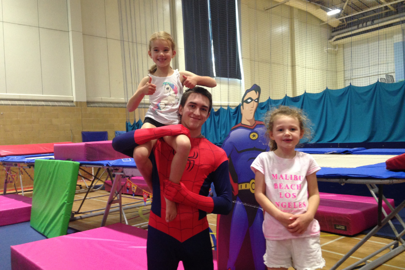 The gymnastics coach dressed as spiderman next to trampolines with two children