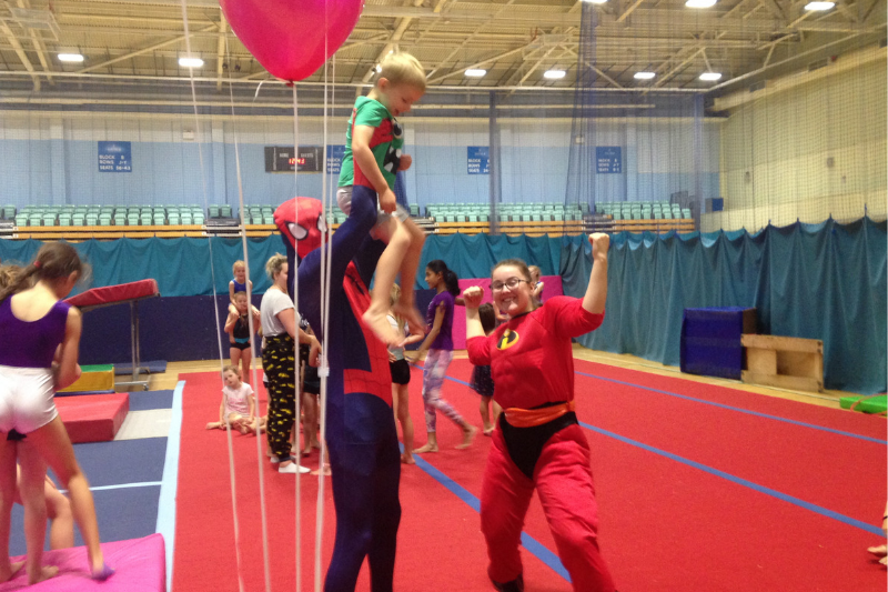A child is lifted up by two coaches dressed as superheroes