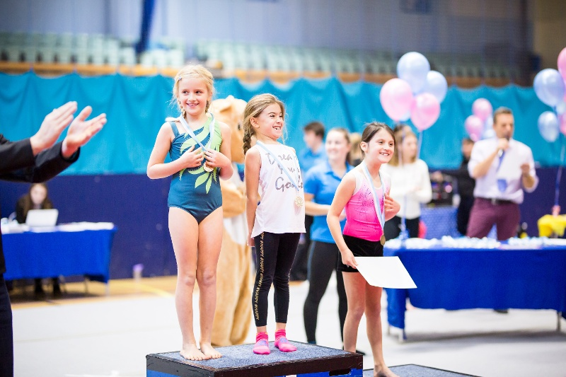 Excited children winning gymnastics medals at the Flair Championships