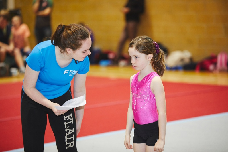 A gymnastics coach helps their student.