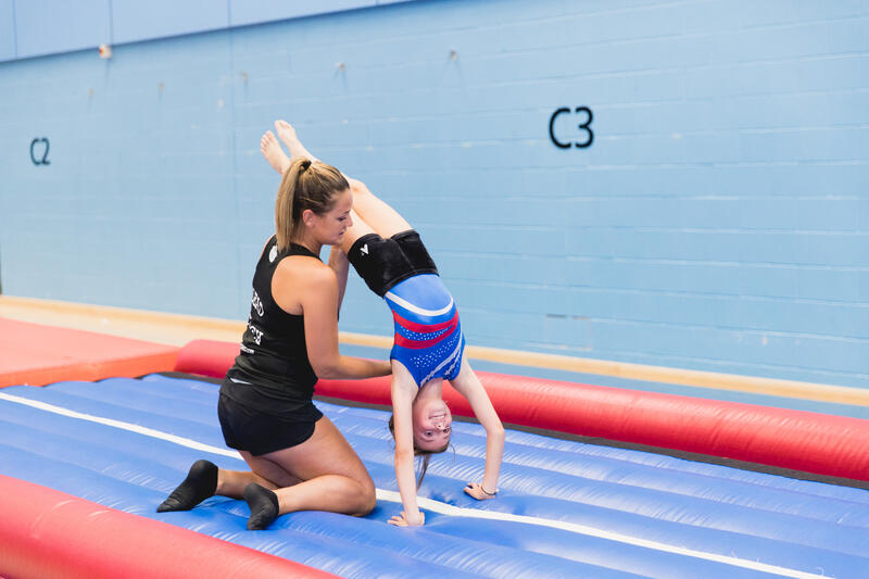 Flair gymnastics coach supports child safely on the air track