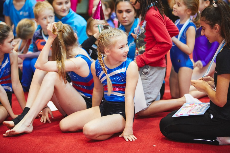 A group of gymnasts sitting and chatting excitedly
