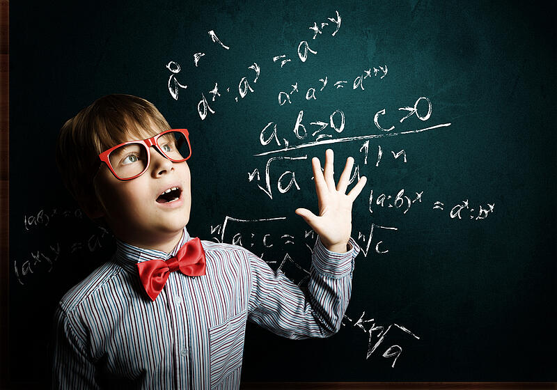 Child Genius boy in red glasses near blackboard - why some parents got upset at the latest series of child genius