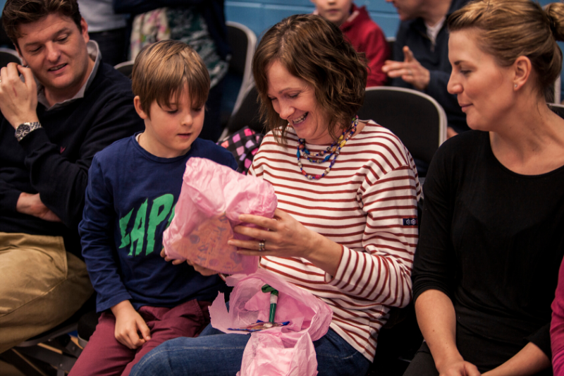A mum opening a present from her child sitting beside her.