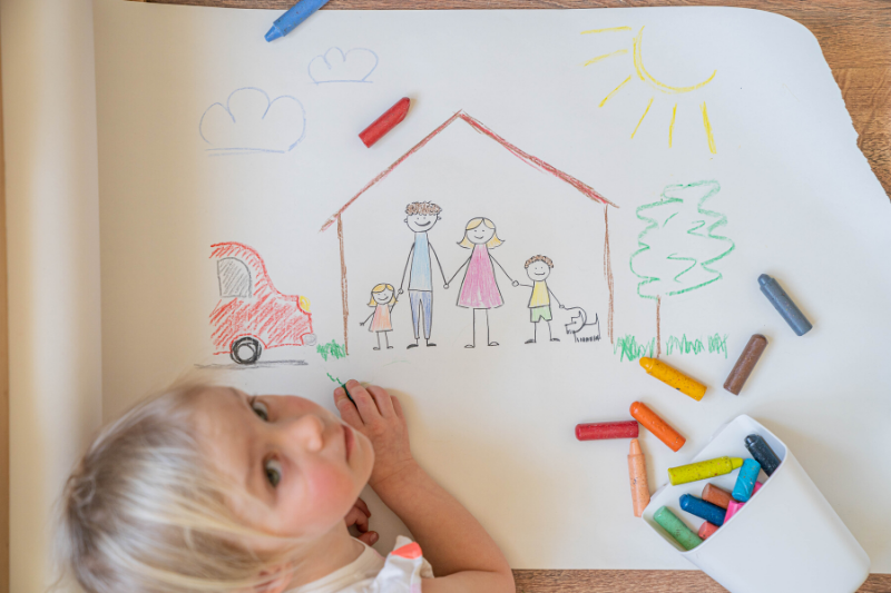 A child drawing a family in a house.