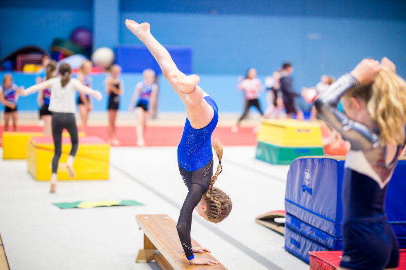 A girl practicing her gymnastics technique at her gym club.